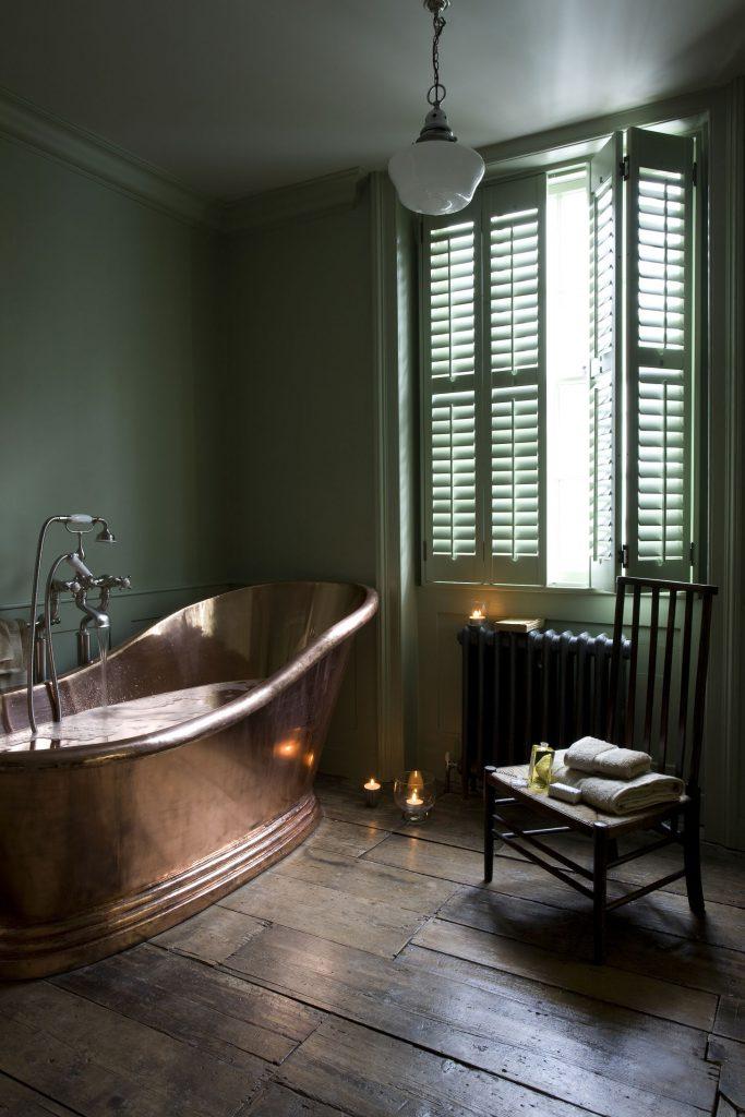 green shutters in bathroom with copper bathtub