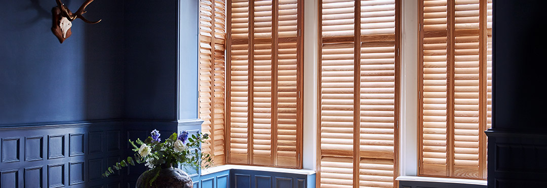 Blue living room decor with wooden shutters by Shutterly Fabulous