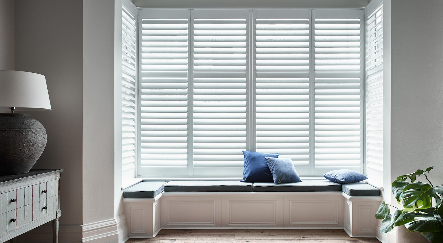 Lounge White window shutters with window seat and blue pillows