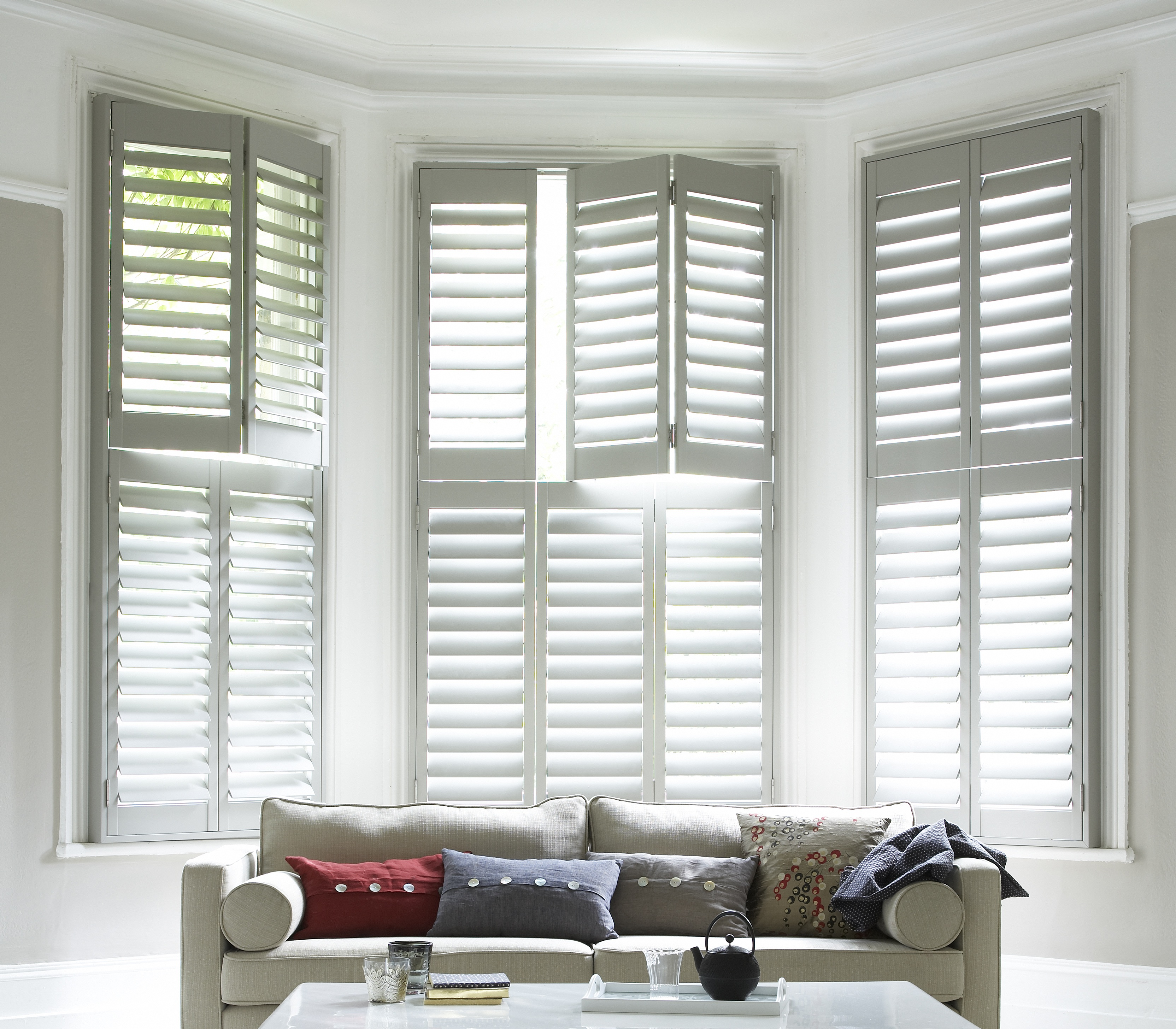 White Tier on tier shell shutters in the living room with grey sofa
